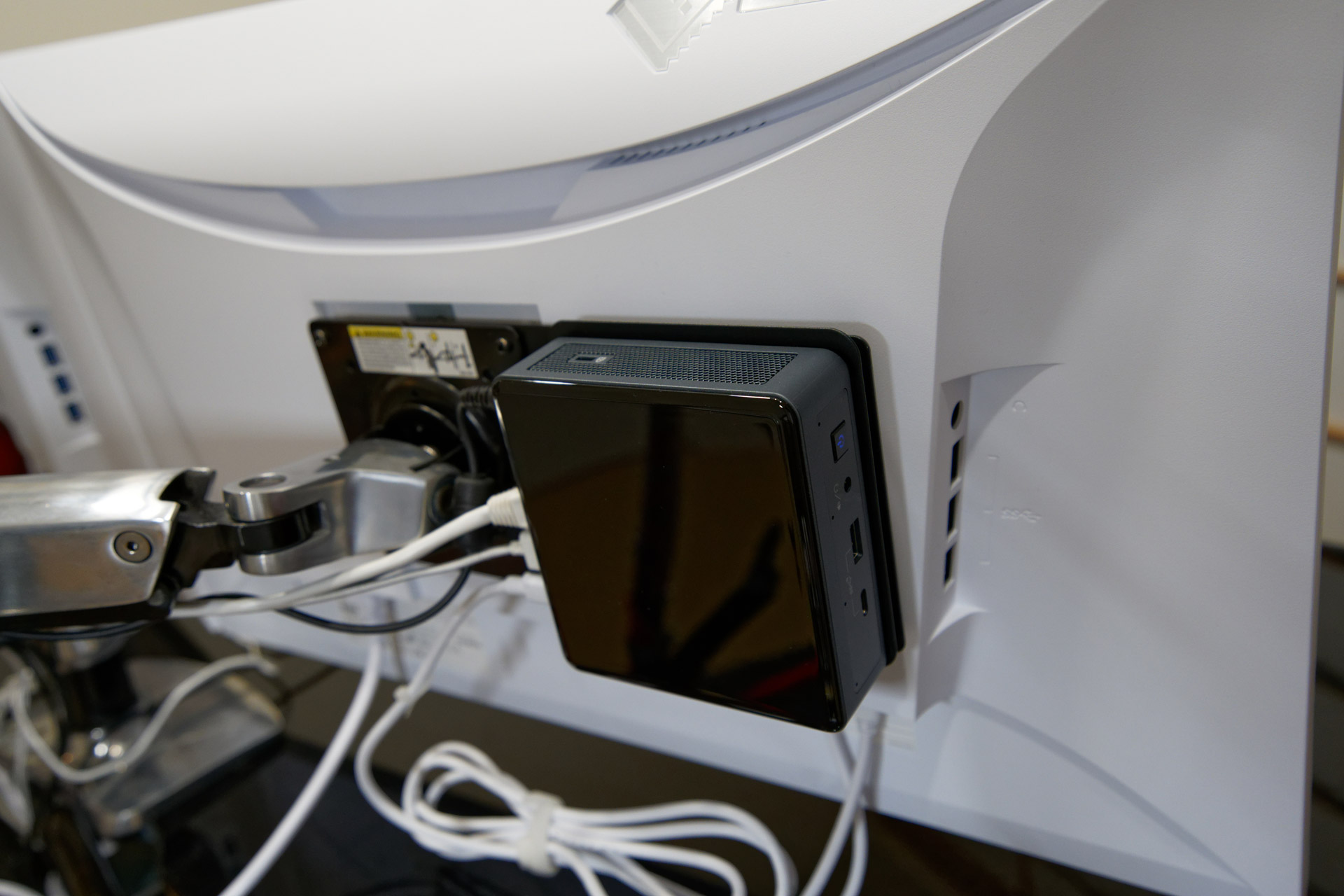 DisplayPort Alt Mode compatible Intel NUC on a bracket attached to the monitor.